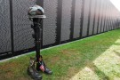 A-helmet-rifle-set-of-dog-tags-and-pair-of-boots-called-a-Fallen-Soldier-Battle-Cross-stands-in-front-of-the-Vietnam-War-Memorial-Wall-rep